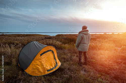 Foto auf Gartenposter Schokobraun A bearded man near a camping tent in orange on the background of nature and the lake. The concept of travel, tourism, camping.