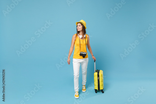 Fotografering  Traveler tourist woman in yellow casual clothes, hat with suitcase photo camera isolated on blue background