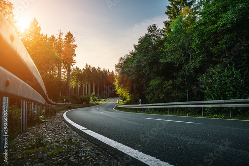 obraz lub plakat Long Curvy Forest Road In Alpine Mountains