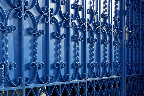 Fototapeta Sunlight and shadow on surface of wrought-iron elements pattern of vintage blue metal gate door decoration, exterior architecture concept obraz