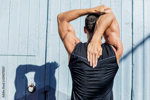 Foto Young Man stretching against a blue wall after a workout