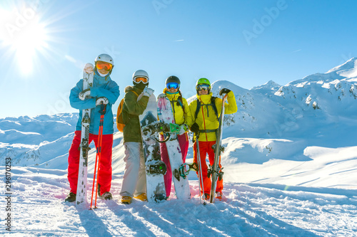 Fotografía  Four happy friends snowboarders and skiers are having fun on ski slope with ski and snowboards in sunny day