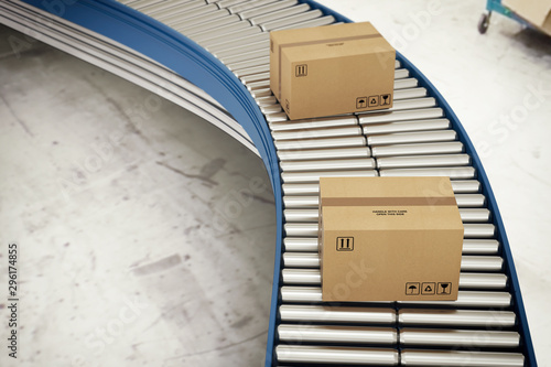 Cardboard boxes on conveyor rollers ready to be shipped by courier for distribut Fototapete