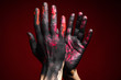Men's hands in black, pink and red paint showing a clapping gesture on a dark background. Right hand in front of left. Close-up studio photo