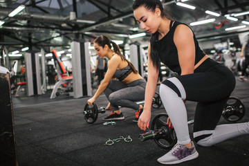 Serious and concentrated young woman put some weight on barbell. Her asian friend repeat actions. They look down. Model prepare for exercise.