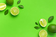 Leinwandbild Motiv Fresh juicy lime and green leaves on bright green background. Top view flat lay copy space. Creative food background, tropical fruit, vitamin C, citrus. Composition with whole and slices of lime