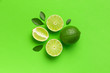 canvas print picture - Fresh juicy lime and green leaves on bright green background. Top view flat lay copy space. Creative food background, tropical fruit, vitamin C, citrus. Composition with whole and slices of lime
