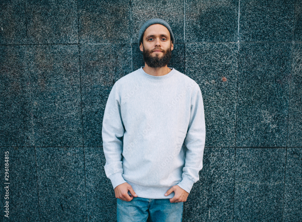 Fototapety, obrazy: City portrait of handsome hipster guy with beard wearing gray blank hoodie or hoody and hat with space for your logo or design. Mockup for print