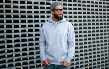 City portrait of handsome hipster guy with beard wearing gray blank hoodie or sweatshirt and hat with space for your logo or design. Mockup for print
