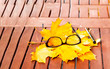Glasses on texture of yellow leaves on wooden table. The concept of the autumn landscape. Close-up