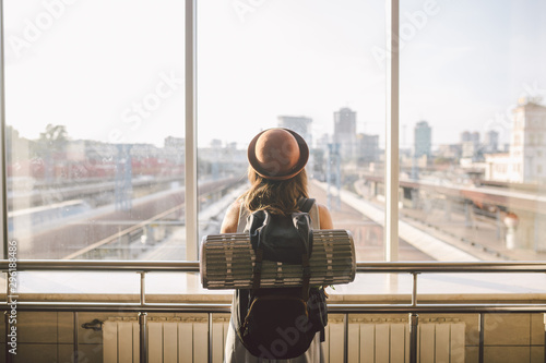 Fotografía  Traveler Rear view woman standing at the window in hall Train Station departure with backpack , Selective focus, Travel concept