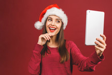 Ney Year Sale! Attractive Woman In Santa Hat And Sweater Holding Digital Tablet Isolated On Red.