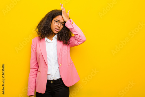 Fotografie, Obraz  black business woman raising palm to forehead thinking oops, after making a stup