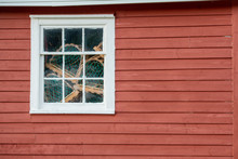 A Red Exterior Clapboard Wall With A Small Nine Pane Window With White Trim. There Are Lobster Traps In The Window Made Of Wood And Green Rope.  The Old Wall Is Textured, Worn And Bright Red In Color.