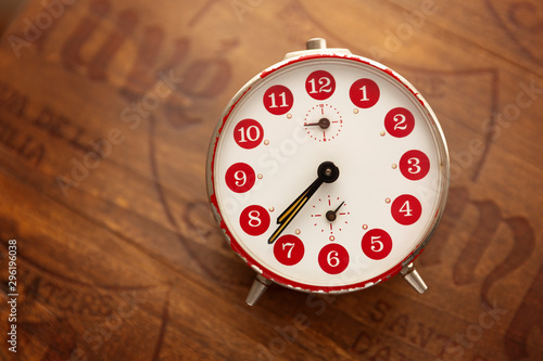 Reloj despertador vintage de color rojo sobre fondo de madera