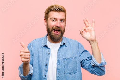 Fotografie, Obraz  young blonde adult man feeling happy, amazed, satisfied and surprised, showing o