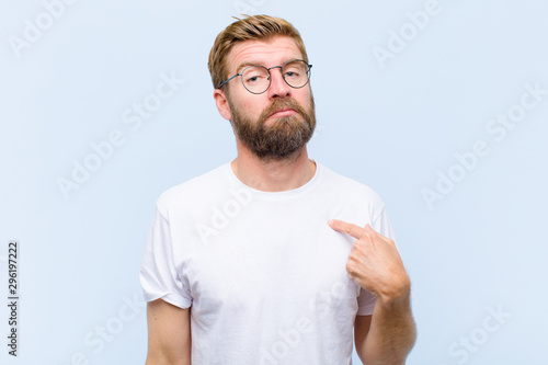 Fotomural  young blonde adult man feeling confused, puzzled and insecure, pointing to self
