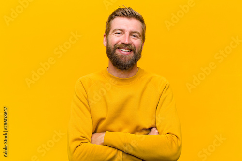 Fototapeta young blonde man looking like a happy, proud and satisfied achiever smiling with arms crossed against orange wall obraz