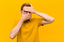 Young Blonde Man Covering Face With Both Hands Saying No To The Camera! Refusing Pictures Or Forbidding Photos Against Orange Wall