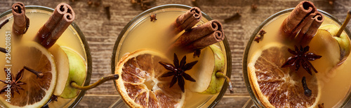 top-view-of-traditional-pear-mulled-wine-in-glasses-with-spices-on-wooden-rustic-table-panoramic-shot