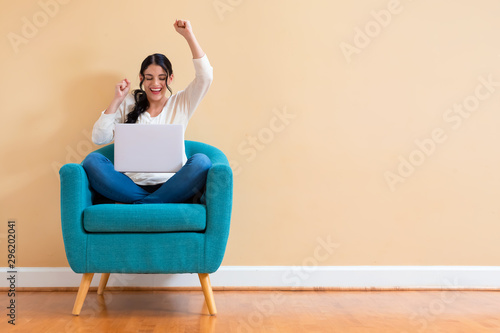 Young woman with a laptop computer with successful pose sitting in a chair Fototapet