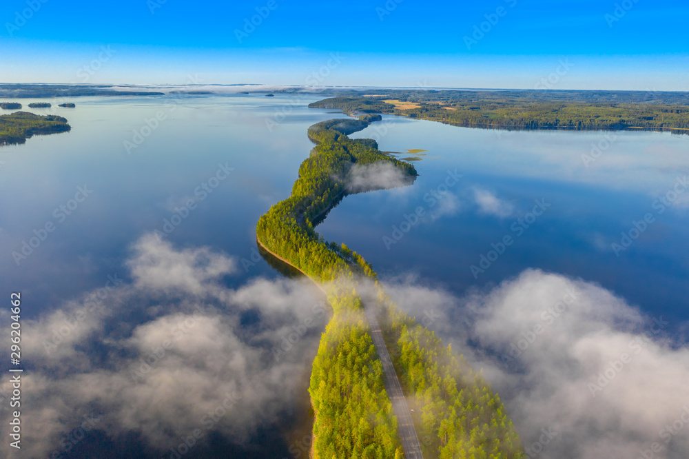 Fototapeta Aerial view of Pulkkilanharju Ridge, Paijanne National Park, southern part of Lake Paijanne. Landscape with drone. Fog, Blue lakes, fields and green forests from above on a sunny summer morning.