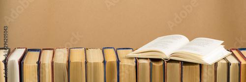 Valokuva  Open book, hardback books on wooden table
