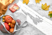 String Bag Full Of Pumpkins, Orange Sweater, Red Gift Box And Autumn Leaves On Marble Background With Autumn Sun Shining Through The Frame And Casting Long Shadows
