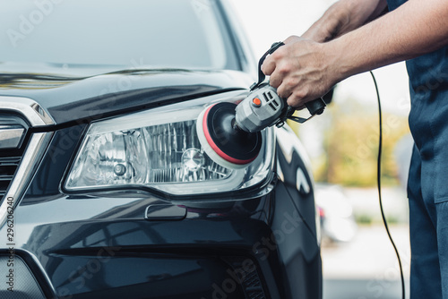 Obraz cropped view of car cleaner polishing headlamp with polish machine - fototapety do salonu
