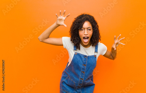 Valokuvatapetti young pretty black woman screaming in panic or anger, shocked, terrified or furi