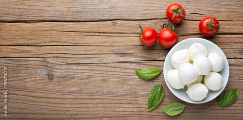 Small mozzarella balls, cherry tomatoes and basil. Top view, space for text.