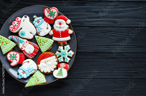 Foto auf Gartenposter Brot Handmade Gingerbread cookies for Christmas, New year on the plate on wooden table. Festive, sweet pastry, delicious biscuits. Home celebration, decoration concept