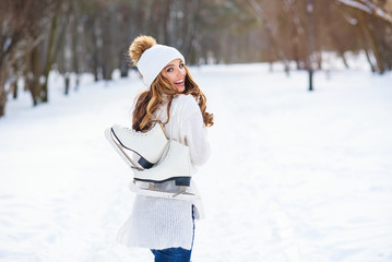 Beautiful woman weared in white sweater and hat with ice skates on the back walks in winter snowy park.
