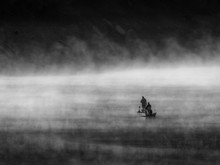 People On The Boat On An Empty Sea Surrounded By Fog
