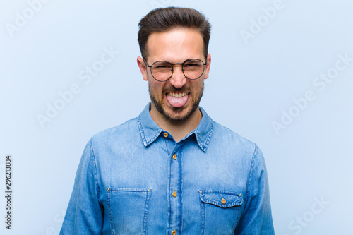 young handsome man feeling disgusted and irritated, sticking tongue out, disliki Tablou Canvas