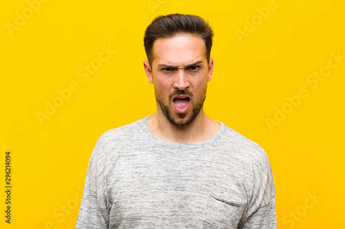 Fotomural  young handsome man looking shocked, angry, annoyed or disappointed, open mouthed