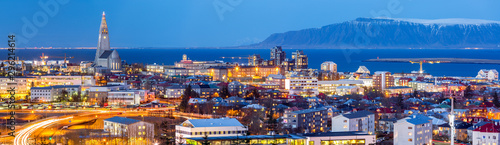 Obraz Aerial view of Reykjavik at dusk. Hallgrimskirkja church dominates the skyline and snow capped mount Esja the background - fototapety do salonu