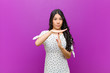 canvas print picture - young pretty latin woman looking serious, stern, angry and displeased, making time out sign against purple wall