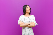 Young Pretty Latin Woman Feeling Happy, Proud And Hopeful, Wondering Or Thinking, Looking Up To Copy Space With Crossed Arms Against Purple Wall