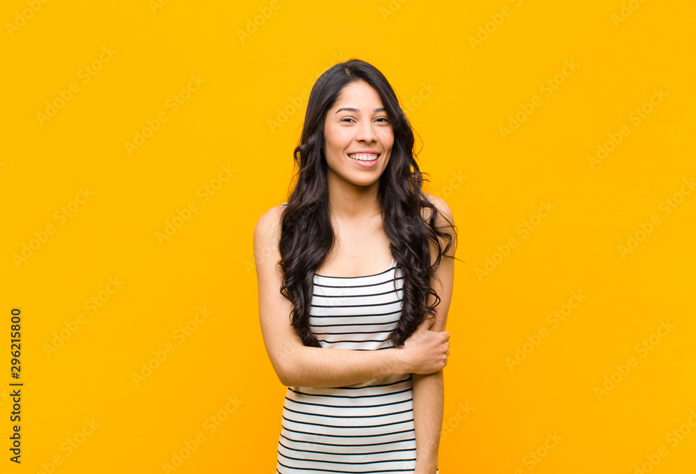 Fototapety, obrazy: young pretty latin woman laughing shyly and cheerfully, with a friendly and positive but insecure attitude against orange wall