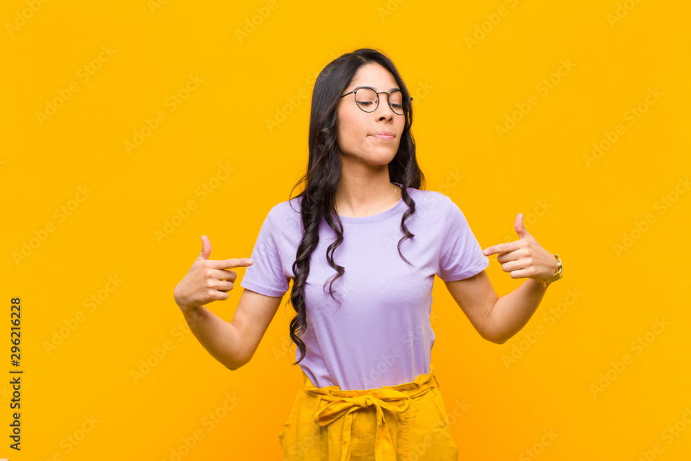 Fototapety, obrazy: young pretty latin woman looking proud, positive and casual pointing to chest with both hands against orange wall