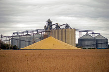A Stockpile Of Harvested Grain In Front Of A Grain Elivator