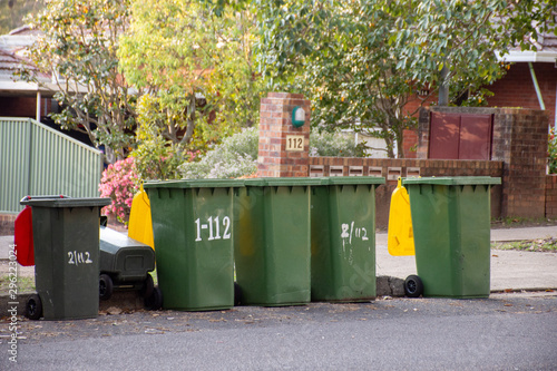 Fototapety, obrazy: Australian garbage wheelie bins with colourful lids for recycling and general household waste lined up on the street kerbside for council rubbish collection