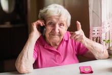 An Elderly Woman Talks On A Mo...