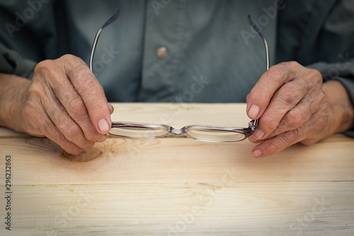 Photo Hands of an elderly man hold glasses