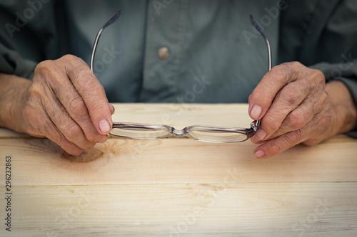Hands of an elderly man hold glasses Wallpaper Mural