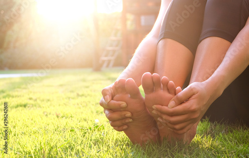Pinturas sobre lienzo  Foot Pain Leg of man sitting on grass in the park holding he feet and stretch the muscles in morning sunlight