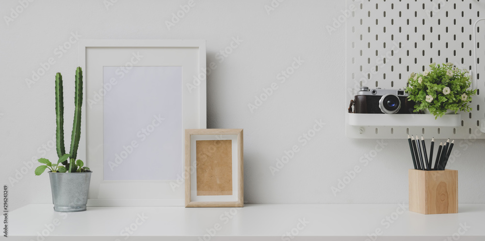 Fototapeta Comfortable workplace with mock up frame and copy space with camera