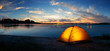 canvas print picture - Orange tourist lit tent by the lake at sunset