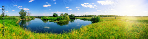 Papiers peints Rivière de la forêt Turn of river in middle of meadow with green grass